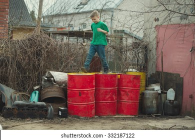 boy walks on barrels from the oil