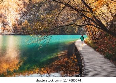 Boy walks on wooden bridge over the mountain lake in Croatia nature park Plitvice Lakes