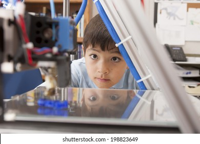 Boy watches machine intently.