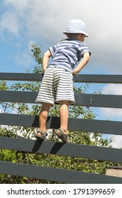 the boy watches the road after entering the gate in the fence