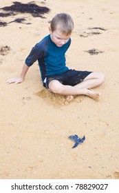 A boy watching a cub Leatherback who hurries into the ocean