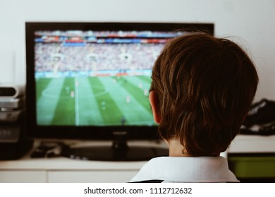 Boy watching a football game on a large TV screen