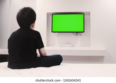 boy watching green screen television on bed