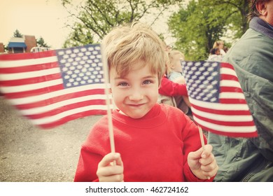 Boy watching a parade holding American Flags