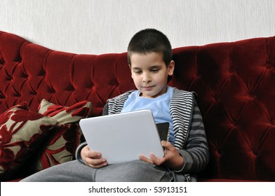 Boy watching portable DVD player in a cafe.