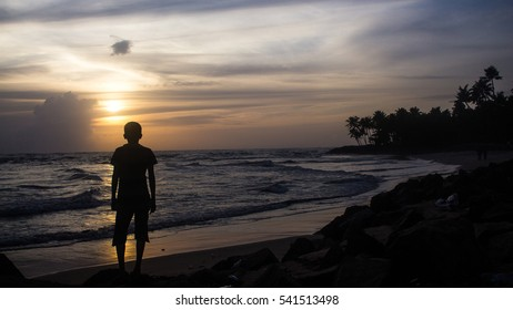 A boy watching sunset at beach. A shot taken from South India.