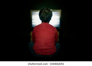 boy watching TV on black background