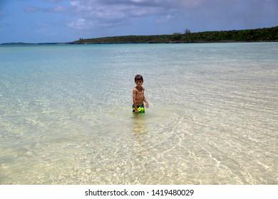 Boy in the water, Ten Bay beach, Eleuthera island, Bahamas.