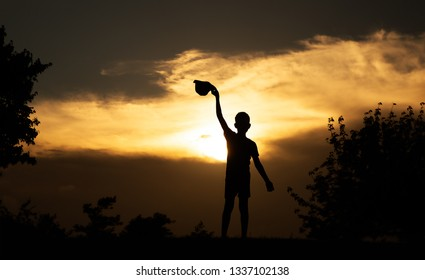boy waving his hat to the setting sun. silhouette of a child at sunset