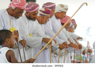 boy waving stick in front of oman men wearing costumes
