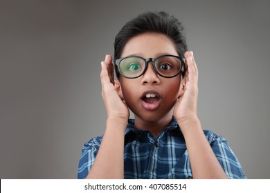 Boy wearing a big spectacle with a shocked expression