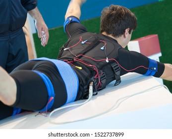 Boy Wearing Black Jacket with Electrode: Muscular Electrostimulation.