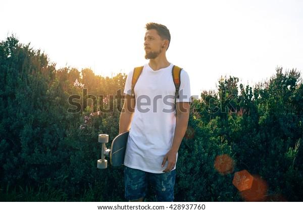 Ein Junge mit einem weißen T-Shirt steht mit seinem Skateboard. Ein Mann mit Rucksack blickt auf grünem Hintergrund zur Seite. Flare Light.