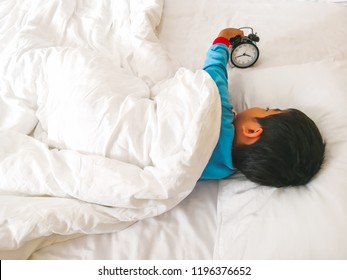 A boy wearing a blue t-shirt lies under the blanket. Hand holding a black watch.Children sleep on a white bed.This picture was shoot from top view.
