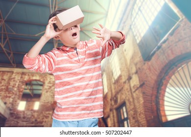 Boy wearing a DIY virtual reality cardboard headset. (Conceptual cross processed image with shallow depth of field)