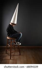 Boy wearing a dunce cap