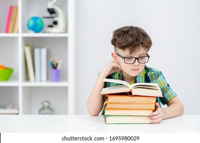 Boy wearing eyeglasses reads book at home. Empty space for text
