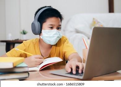 Boy wearing face masks online study homeshcooling at home.