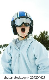 Boy wearing helmet and ski goggles, snow-covered, open mouth