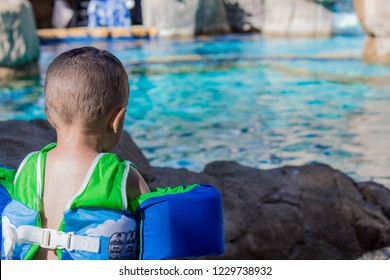 Boy wearing life jacket flotation device by a swimming pool, vacation water safety.