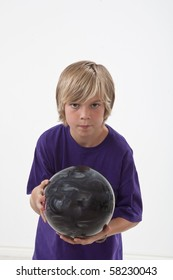 Boy wearing purple shirt ready to roll bowling ball.