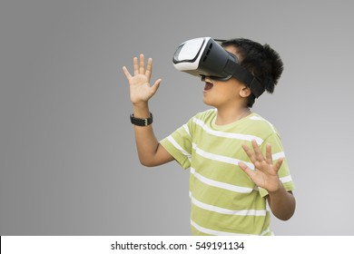 The boy wearing virtual reality goggles on the gray  background