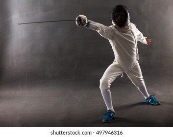 Boy wearing white fencing costume and black fencing mask standing with the sword practicing in fencing.