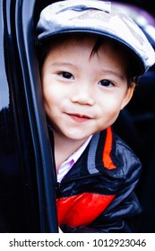 The boy wears a black-red jacket and flat cap, at the door car