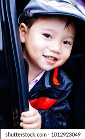 The boy wears a black-red jacket and flat cap, at the door car.