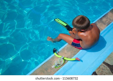 The boy wears fins on the edge of the pool. Next to it is a mask. Blue water.