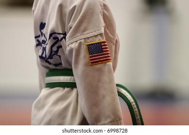 A boy wears the taekwondo uniform with green stripe belt.