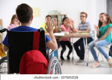 Boy in wheelchair with classmates at school