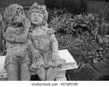 Boy Whispering Secrets to Girl in a Garden