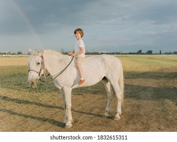 Boy in white clothes in a field with a horse