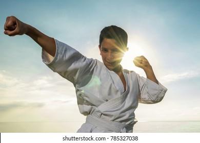 Boy in white kimono during karate exercises in outdoor.