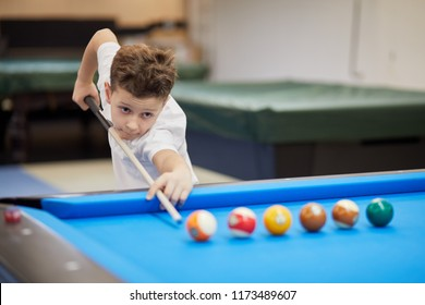 Boy in white polo-neck shirt aims ball with cue stick in billiard club.