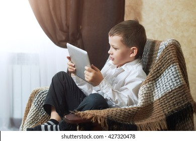 boy in white shirt and black pants, plays on the tablet their hand up wins happy smiles