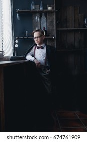 A boy in a white shirt with a bow tie, trousers, suspenders and glasses is sitting by the window behind the bar
