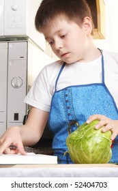 Boy in white shirt at kitchen with cabbage and cookbook
