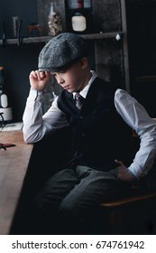 A boy in a white shirt, waistcoat, trousers and a cap sits at the window behind the counter