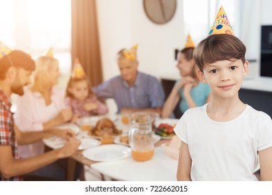 A boy in a white T-shirt and festive hat poses before the festive table, for which his relatives gathered. They celebrate the birthday of a little girl