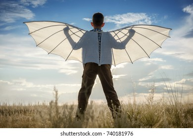 Boy with wings in the field in the afternoon against the blue sky