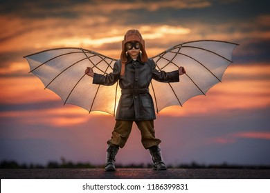 Boy with wings at sunset imagines himself a pilot and dreams of flying