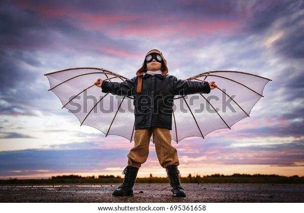 Un garçon avec des ailes au coucher du soleil s'imagine un pilote et rêve de voler