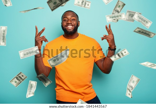 Boy wins money. Amazed and surprised expression face. Light blue background.