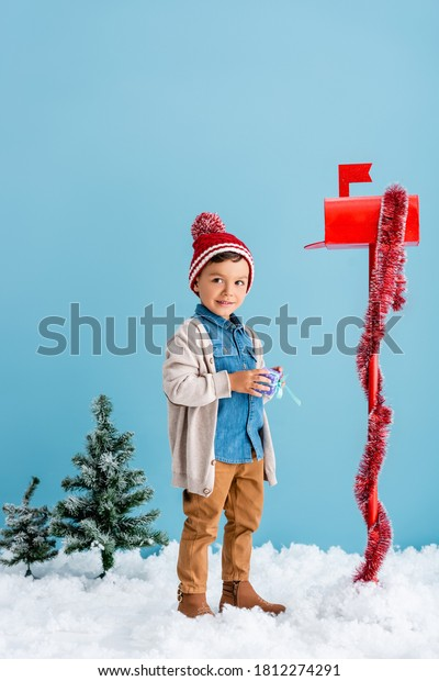 boy in winter outfit holding present near red mailbox while standing on blue