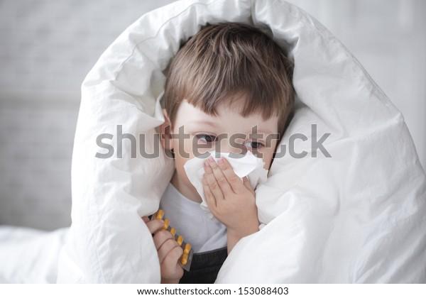 menino limpa o nariz com um lenço