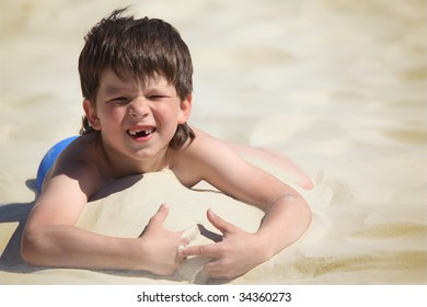 boy without fore teeth lies on sand