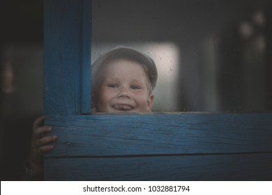 boy without front teeth is very fun and cute smile looking through the glass
