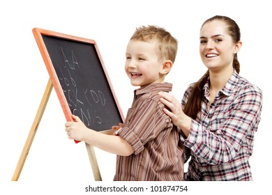 A boy, woman and blackboard.The boy learns to write on the blackboard. He is very happy and joyful. A woman is smiling and glad.